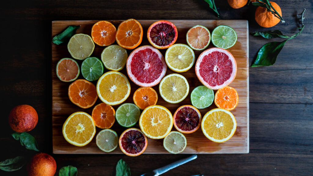 Slices of Oranges, Grapefruit, Lemon on a Wood Board - Fruits Images With Top View