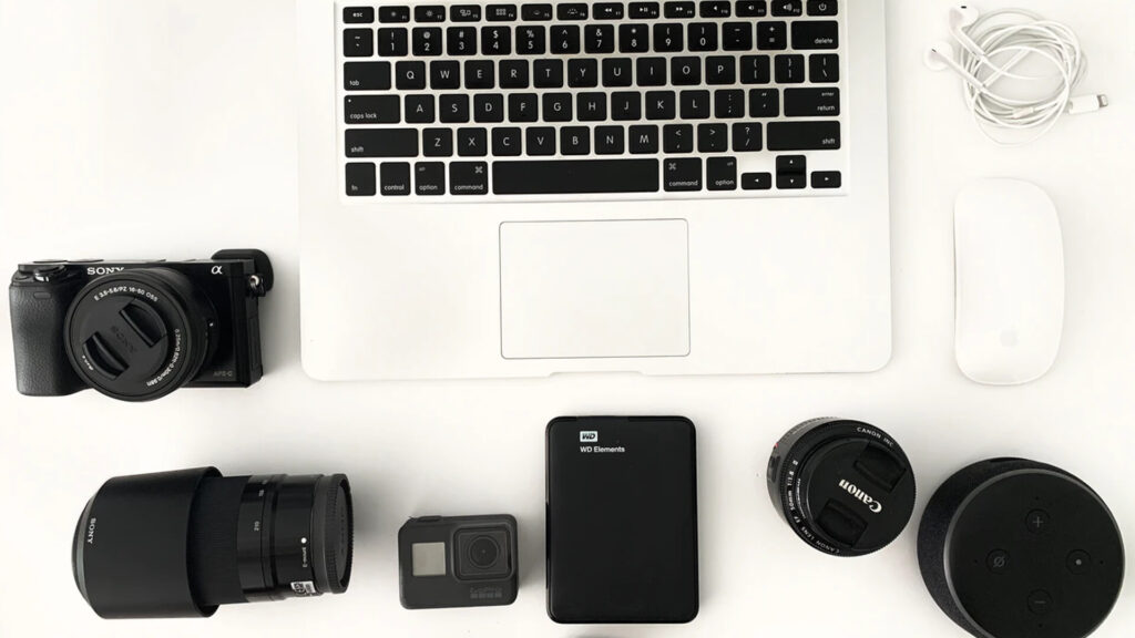 Laptop, Mouse, Camera, Camera Lenses on Table