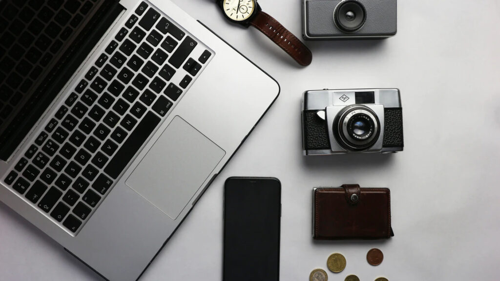 Laptop, Watch, Camera, Wallet, Mobile, Coins on Table